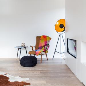 totaal project stoel met kleurrijk deken, ingebouwd haardmeubel en een design lamp, spot