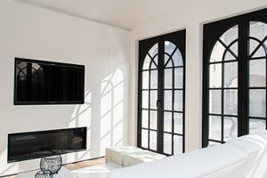 ingebouwde haardstede en flatscreen televisie weggewerkt in een strak wit afgeweekte muur en stalen raam constructie