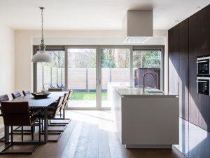 vrijstaand keukenblok met tafels en stoelen. Een design lamp boven de tafel.