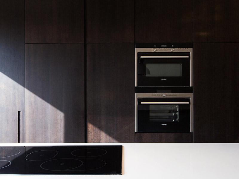 Vooraanzicht van een keuken met keukentoestellen. Donker eiken inbouw kasten.