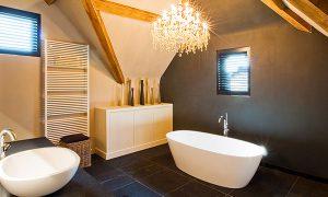 interieur projecten badkamer. Sfeervolle landelijke badkamer met een mooie kroonluchter boven het bad