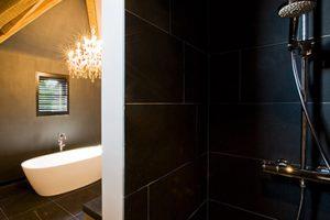 landelijke badkamer met een kroonluchter boven het bad en zwarte betegelde douche