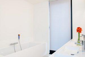 strak witte badkamer met inbouwkasten wit ligbad en een vrolijke bloem