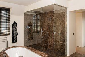 bruin marmeren badkamer met bruin marmer bad en glazen douchecabine