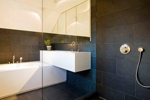 badkamer met zwarte tegels en een glazen douchecabine en een wit ligbad