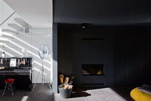 piano in een zwart wit gekleurde kamer met een open haard en gele zitzak
