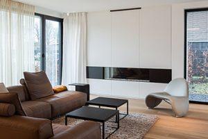 royaal woonkamer met lederen bruine hoekbank en haardmeubel met ingebouwde kasten