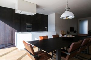 donkere keuken kast met wit keukeneiland en hanglamp boven de eetkamer