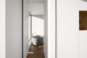 open pivot deur met uitzicht op een losstaand ovale badkuip