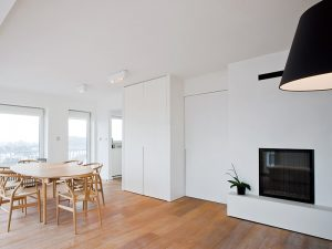 licht eikenhout keukentafel met stoelen in een appartement met witte inbouwkasten