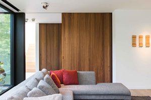 robuust houten schuifdeuren met op de voorgrond een grijs gestoffeerde hoekbank