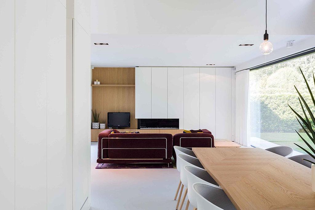 massief houten tafel met zes designstoelen en uitzicht op een ingebouwde kast