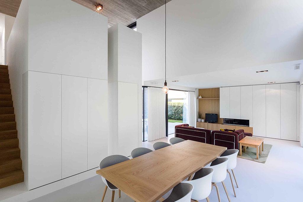 robuuste houten tafel met acht kuipstoelen en uitzicht op woonkamer