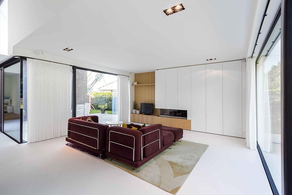 bordeaux kleurige hoekbank op een tapijt hoge ramen en inbouwkasten en haardmeubel