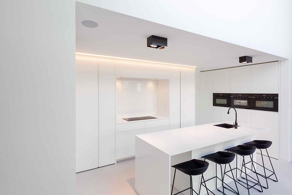 zwart wit keukenblok met vier moderne zwarte barstoelen en ingebouwd keukenapparatuur