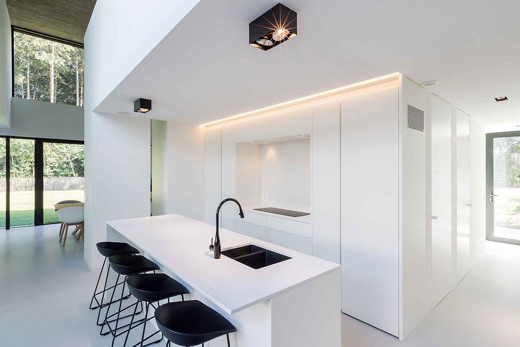 keukenblok met zwart moderne designstoelen en een ledstrip en spot verlichting op het plafond