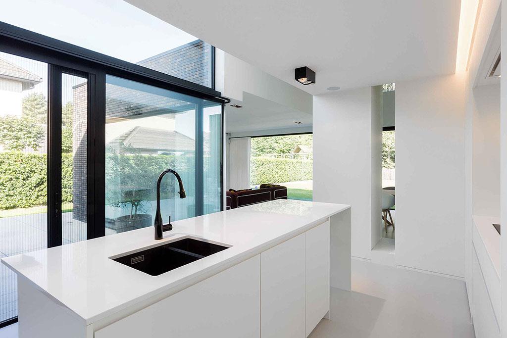 wit keukenblad met rvs wasbak en een zwarte kraan