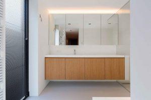 zonwerende raamdecoratie in de badkamer dressing van natuurhout en vier spiegels