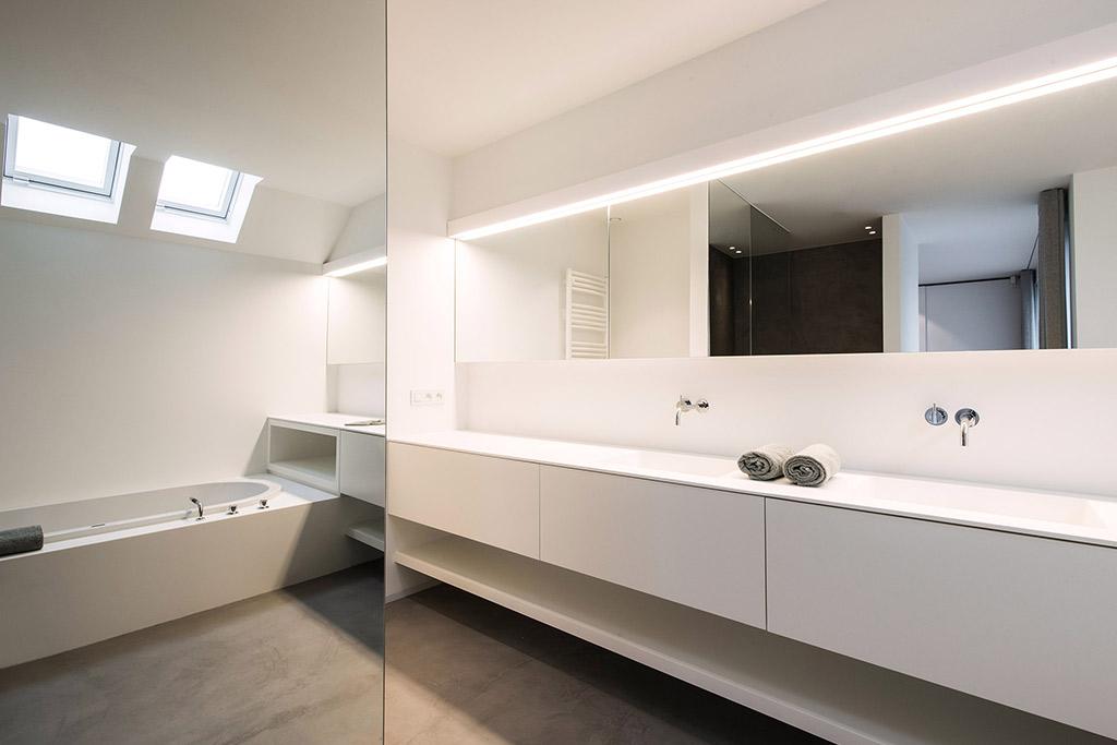 afbeelding van de badkamer met het bad in de reflectie van de spiegel