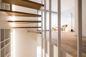 overzicht van de tussenverdieping met uitzicht tussen de trap door naar een ligstoel ontwerp van le corbusier