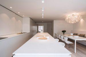 Wit keukenblok, keukeneiland, lange rechthoekige tafel en 6 eetkamer stoelen