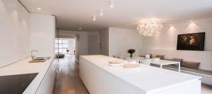 overzicht afbeelding van een tijdloos witte keuken met een keukeneiland en blad van marmer. De keuken in de duplex woning van Rocco Granata