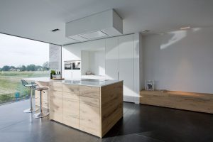 modern robuust keukenblok met twee barstoelen en een afwerking in venetiaans fineer