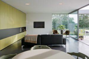 vooraanzicht van een ruime woonkamer met olijfkleurige muur