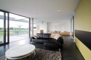 ruime moderne woonkamer met olijf tinten en een zwarte hoekbank