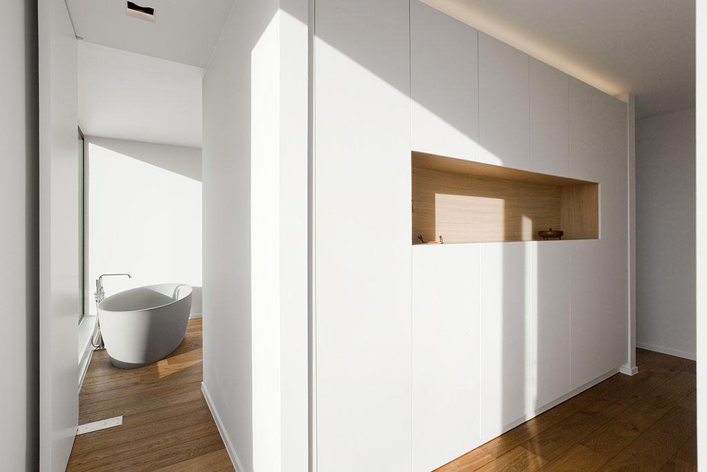 op maat gemaakte inbouwkast, parket eiken vloer en een strak badkuip design
