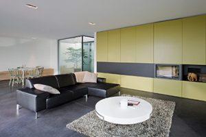 De woonkamer van Interieur totaalproject keersmaekers met olijfgroene inbouwkasten en een ingebouwde haardmeubel met een hardstenen vloer.