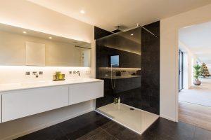 badkamer met een luxe douchecabine en zwarte tegels
