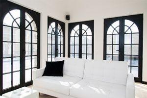 Interieur totaalproject Broeck, een wit bankstel met hoge ramen verwerkt in stalen frames