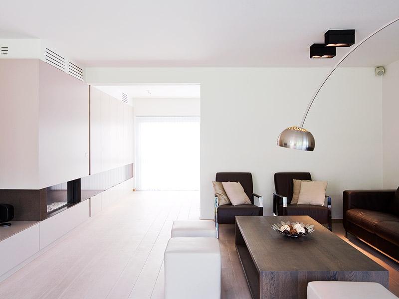 groot salon met moderne hanglamp en ingebouwde spots. De bruin ledere zetel staat recht tegenover het bruin gekleurde haardmeubel