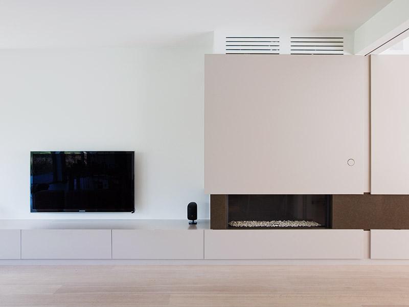 zwevende televisie boven een tv meubel en op maat gemaakte kasten en haardmeubel