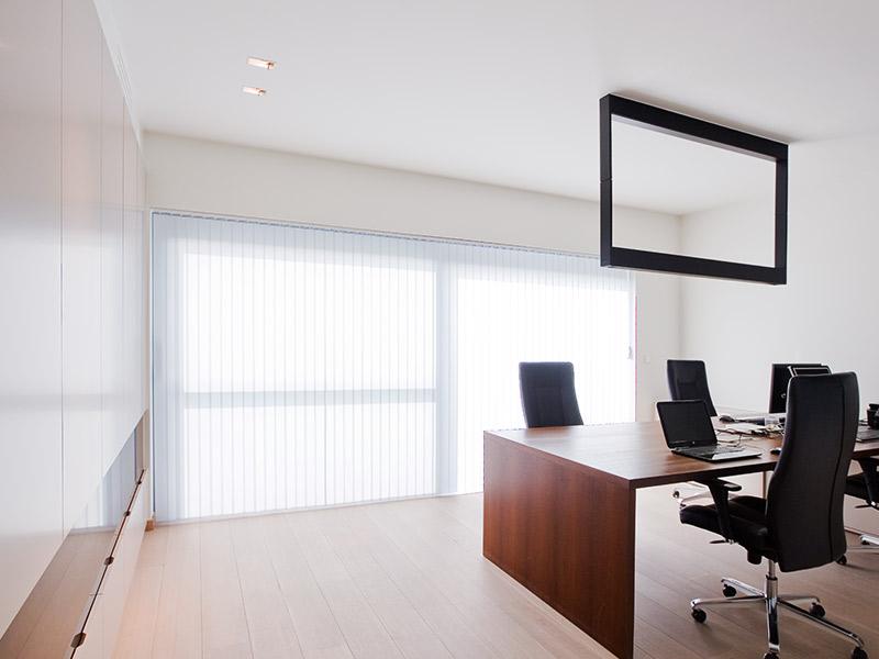 bureau met witte raamdecoratie en zwarte design lamp boven het meubel