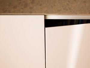 detail van een open deur van een kast met een marmerblad