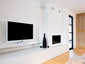flatscreen televisie tegen de muur met een witte dressoir eronder, ingebouwde speakers in de muur en een wit haardmeubel