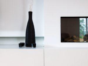 zwarte vaas naast een haardmeubel