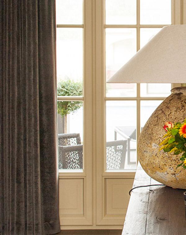 Interieur projecten vensterdecoratie. Raamdecoratie van een stoffen gordijn en lamp op de tafel