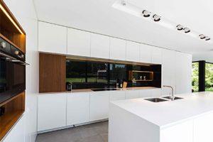 Keuken Maes. Prachtig witte design keuken met houten details en een wit keukeneiland