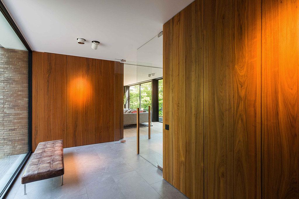 De inkom van een riante villa met massief eiken wand en glazen deur