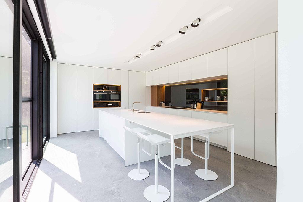 tijdloze witte keuken met vier moderne krukken aan het keukenblad