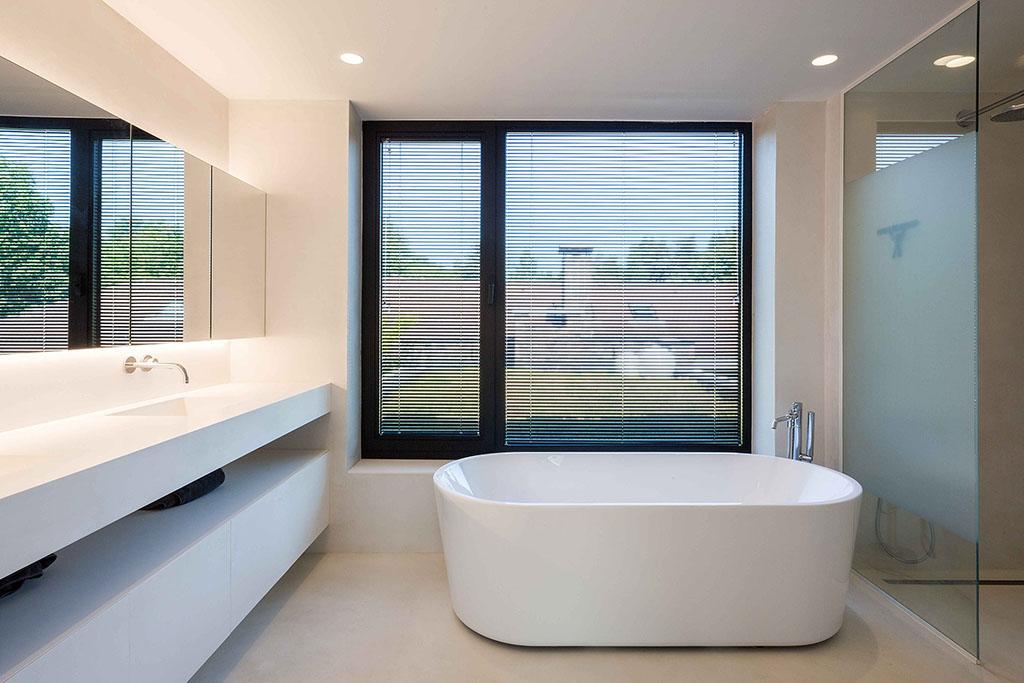 badkamer met een ovaal bad en raamdecoratie