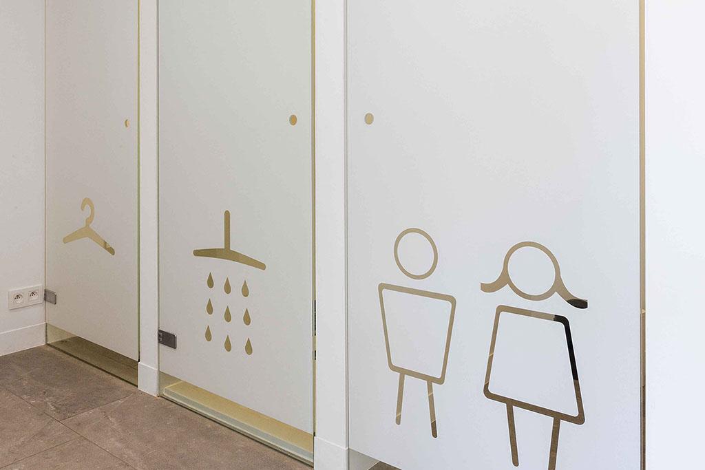 witglazen deuren met iconen voor kleding, douche en toilet man of vrouw