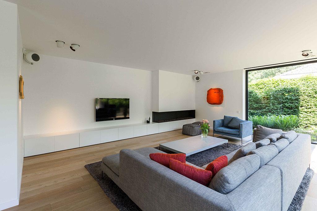 de woonkamer bekeken van achter de hoekbank naar de flatscreen tv