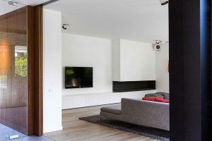 een tapijt, gedeelte van de hoekbank en wandkast waar de televisie boven hangt