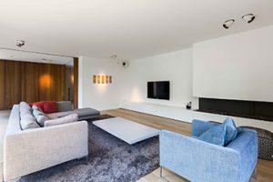 overzichtsafbeelding interieur totaalproject maes. Een woonkamer met een gestoffeerde bank, haardmeubel, laag salontafel en warme kleuren door de donker eiken schuifdeur.