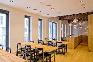 kantine ruimte van mcgregor te antwerpen met zwarte stoelen en hardhouten licht eiken tafels