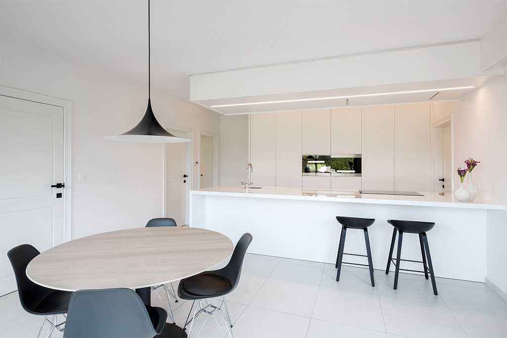 ovale eettafel met een zwarte hanglamp in de keuken